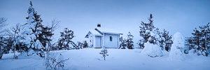 Aalistunturin palovartianmökki lumisessa iltahämärässä
