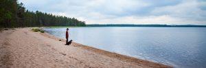 Kuvassa mies ja koira seisovat Tirroniemen hiekkarannalla